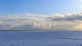 The coast of Baltic sea. Landscape landscape of the Baltic Sea coast in winter with beautiful clouds and blue sky on a sunny day, water and stones, covered with Stock Photography
