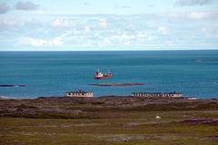 Coast of Barents Sea. Russian coast of Barents Sea with abandoned houses and big red ship Stock Photos