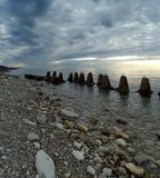Coast of the Black Sea, Sochi. Winter of 2018, cloudy day, iron-concrete coastal protective structures, wild beach. Stones, water, clouds Stock Photos