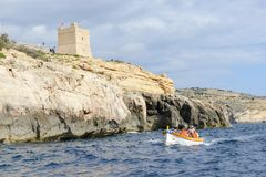 The coast at Blue Grotto in the Malta island. Blue Grotto, Malta - 3 November 2017: tourists visiting the coast by boat at Blue Grotto in the Malta island Royalty Free Stock Image