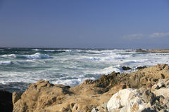 Coast of California: rocks, ocean and blue sky. Coast of California, Monterey bay: rocks, ocean with waves and blue sky Stock Photo