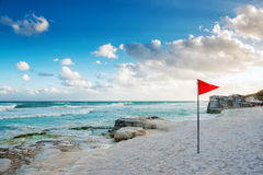 Coast of the Caribbean sea with a red flag on the beach. A storm warning stock photos