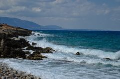 Coast of Crete and sea waves in Greece. Beautiful turquoise sea with rocky coast in Crete with cloudy sky Stock Photo