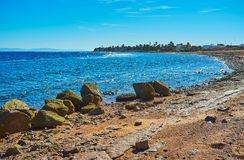The coast of Dahab, Sinai, Egypt. The rocky coastline of Aqaba gulf with boulders, protecting beach from the strong waves, Dahab, Sinai, Egypt stock images