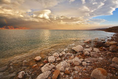 Coast of the Dead Sea in Israel. In a spring thunder-storm. Coastal stones are covered by salt Royalty Free Stock Photos