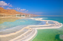 The coast of the Dead Sea. Israeli coast of the Dead Sea. The path from salt picturesquely curls in salty water. Hotels are reflected in smooth water ashore Stock Images