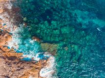 Coast of desert island with blue turquoise water beats on rocky reef. Aerial top view. Coast of desert island with blue turquoise water beats on rocky reef stock images