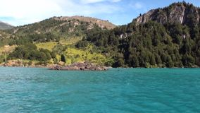 Coast of green mountain river view from boat in Patagonia Argentina. Unique landscape of wildlife. Beautiful nature background. Travel and tourism in stock footage