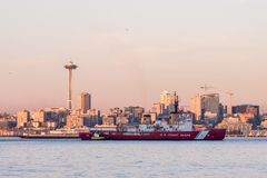 Coast Guard boat in Elliott Bay with sunset over downtown skyscrapers in Seattle, Washington, USA. stock photography