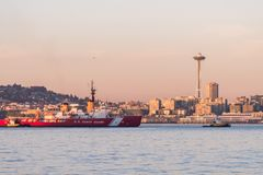 Coast Guard boat in Elliott Bay with sunset over downtown skyscrapers in Seattle, Washington, USA. royalty free stock photography