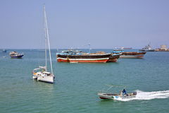 Coast Guard boat goes by luxury sailing boat, fishing and cargo ships Royalty Free Stock Image