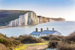 The Coast Guard Cottages and Seven Sisters Chalk Cliffs just outside Eastbourne, Sussex, England, UK. The Coast Guard Cottages and Seven Sisters Chalk Cliffs Stock Photo