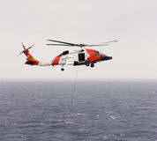 Coast Guard Helicopter. A United States Coast Guard helicopter lowering a rescue basket during an air-to-sea rescue mission. The Blackhawk copter was hovering royalty free stock photo