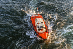 Coast Guard lifeboat. Orange and white coast guard lifeboard photographed from bird's eye-view, visible sunset sunrays, sea and waves royalty free stock image