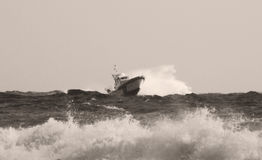 The Coast Guard patrol boat along the sea. Rescuer on the beach. The sea is very rough and the rescue teams looking for a missing helicopter while the fire Royalty Free Stock Images