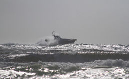 The Coast Guard patrol boat along the sea. Rescuer on the beach. The sea is very rough and the rescue teams looking for a missing helicopter while the fire Royalty Free Stock Photo