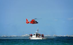 Coast guard rescue. Helicopter and boat performing a rescue operation at sea Stock Image