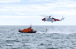 Coast Guard. UK coast guard helicopter on a rescue mission, with lifeboat and man Royalty Free Stock Image