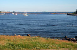 Coast of Gulf of Finland. Sea landscape – coast, sea, stones, yachts and sky royalty free stock photography