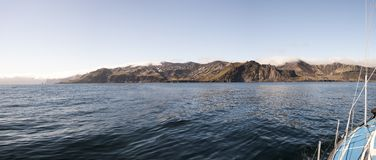 Coast of Jan Mayen island from the sea. Coast of the volcanic island of Jan Mayen, Norway, viewed from the sea. Panoramic image obtained by stitching multiple Stock Photography