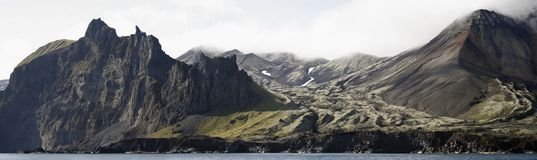 Coast of Jan Mayen island from the sea. Coast of the volcanic island of Jan Mayen, Norway, viewed from the sea. Panoramic image obtained by stitching multiple Stock Images
