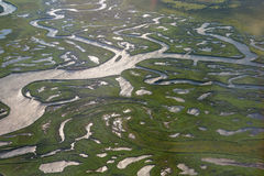Coast of the Kamchatka Peninsula is cut by water arteries of Pacific Ocean. View from plane. Royalty Free Stock Photos