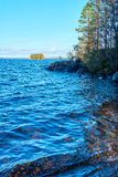 Coast of a lake with blue water, trees and granite stones. Colorful island with autumn colors on a background. royalty free stock images