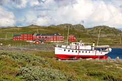 Coast of lake Bygdin with boat and traditional norwegian buildings stock photo