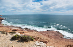 Coast Line at Red Bluff. Overhead view at Red Bluff of the red sandstone coast line and turquoise Indian Ocean seascape with foamy waves under a cloudy sky on Royalty Free Stock Photo