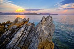 Coast, mountain and sea. Rocky sunset at sea, colorful seascape in Greece, steep beach, Steep cliffs and turquoise sea, inaccessible landscape, abrupt rocks Stock Images