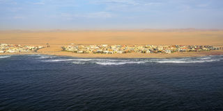 The coast in Namibia. Aerial view on the coast in Namibia and modern districrt of the city Walvis Bay in the Namib desert, Atlantic ocean, Africa royalty free stock photos