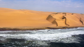 The coast in Namibia. Aerial view on the coast in Namibia where dunes of the Namib desert meet with Atlantic ocean, Africa royalty free stock image