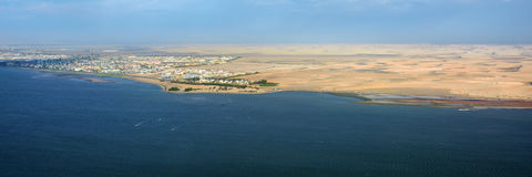 The coast in Namibia and panorama of the city Walvis Bay i. Aerial view on the coast in Namibia and modern districrt of the city Walvis Bay in the Namib desert Royalty Free Stock Photos