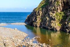 Coast near Sao Jorge, Madeira Island, Portugal. The mountain river flows into the ocean Stock Photography