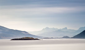 Coast of  Norway sea in clouds of haze. Beacon on a rock. Cloudy Nordic day on Lofoten islands Royalty Free Stock Photo