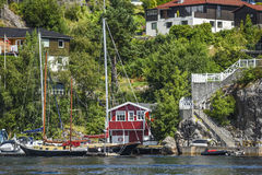 Coast of Norway, with yacht and charming cottages in the backgro. Und, summer Stock Image