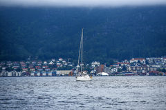 Coast of Norway, with yacht and charming cottages in the backgro. Und, summer, cloudy sky Royalty Free Stock Photo