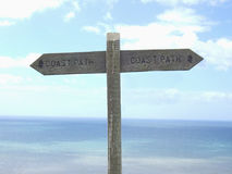 Coast path. A sign giving directions of the coastal path, shot against the sea Stock Photography