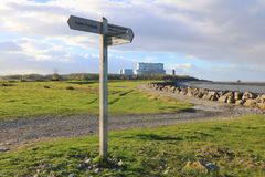 Coast path and power station. A wooden footpath sign and nuclear power station at Hinckley Point in Somerset, England Royalty Free Stock Photography