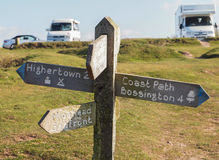 Coast Path Sign and Camping Park. Old wooden sign of the coast path along the Exmoor National Park in Somerset, England.  Showing directions and distances to Stock Photography