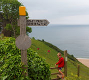 Coast Path Sign and young walker, Strete, Devon, UK Royalty Free Stock Images