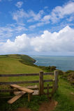 Coast Path and Stile. Path and stile on a coastal footpath with the sea and cliffs beyond royalty free stock image