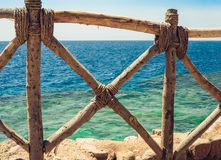 Coast of the Red Sea with a wooden fence and sun umbrellas in Sharm El Sheikh, Egypt royalty free stock photos