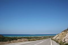 Coast Road to Monolithos. An open coast road winds up Rhodes island from Prassonissi to Monolithos. Stunning clear blue sky fills the shot Royalty Free Stock Photography