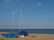 At the coast with sailing boats. Stones ion the beach and deep blue water and sky royalty free stock photography