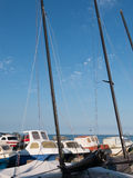 At the coast with sailing boats. Stones ion the beach and deep blue water and sky stock image