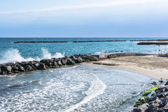 The coast of Sanremo, Italy. Sand beach and breakwater along the coast of Sanremo, Italy Stock Photos