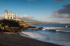 Coast of Sao Roque, Sao Miguel Island, Azores Islands, Portugal. Coast of Sao Miguel Island, city Sao Roque. Church on a hill. Beach in the foreground. Cloudy stock image