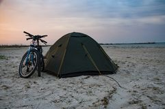 Recreation of a biker on the beach in a tent. Coast of the Sea of Azov at sunset. Bicycles near the tent are waiting for a new day Stock Photo