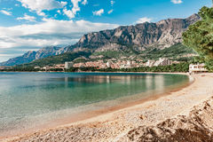 Coast sea and beach below mountain Biokovo in town of Makarska Stock Image